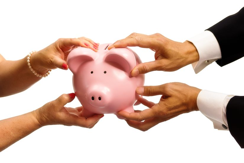 A woman's hand and a man's hand fighting and pulling over money, saving in a piggy bank. Concept photo illustrating difficulties in human relationship, or business partnership, or marriage relationship. Photographed on white background.